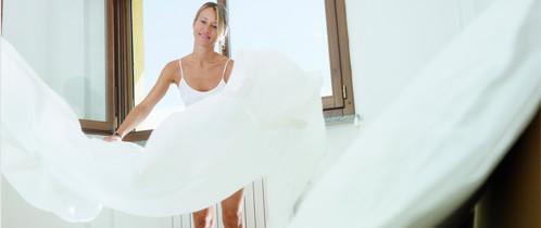 Vrouw laat een dekbed luchten